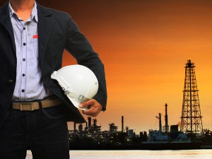 engineering man and safety helmet standing against beautiful dusky sky of oil refinery plant scene use for energy of fossil fuel and industry topic background