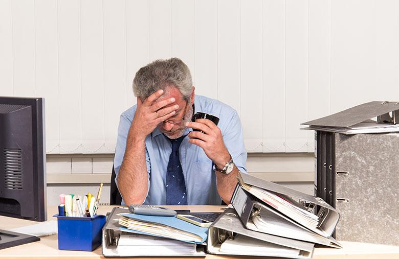 Mann mit Burnout Stress am Schreibtisch